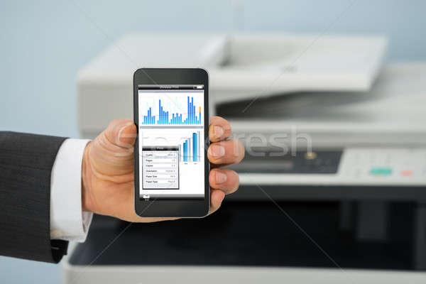 üzletember mobiltelefon nyomtatás grafikon papír közelkép Stock fotó © AndreyPopov