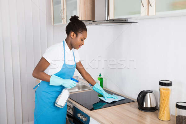 Female Janitor Cleaning Induction Stove Stock photo © AndreyPopov