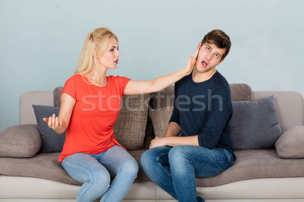 Woman Slapping Man While Quarreling At Home Stock photo © AndreyPopov