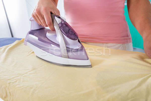 Woman Hand Ironing Cloth On Ironing Board Stock photo © AndreyPopov