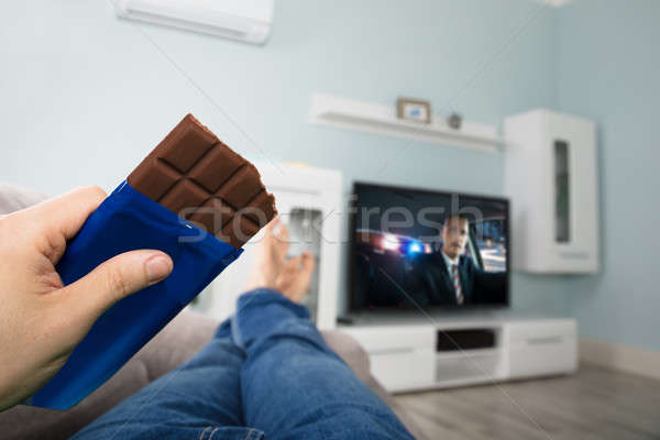 Person Enjoying Chocolate While Watching Television Stock photo © AndreyPopov