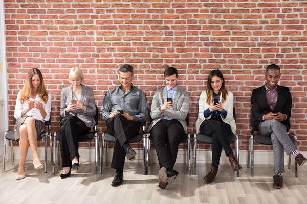 Mensen wachten sollicitatiegesprek mobiele telefoon rij Stockfoto © AndreyPopov