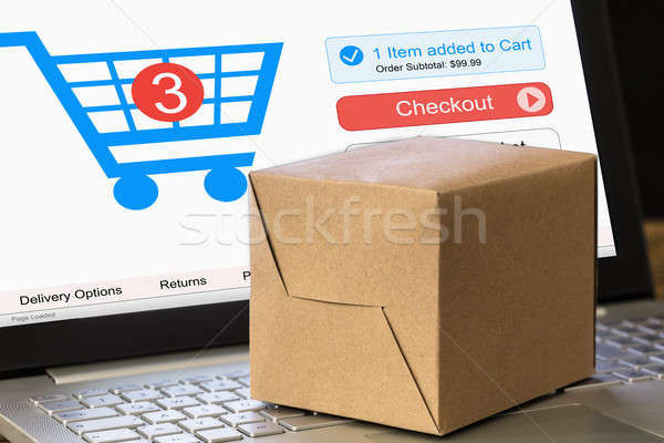 Cardboard Box On Laptop With Shopping Cart Displayed On Screen Stock photo © AndreyPopov