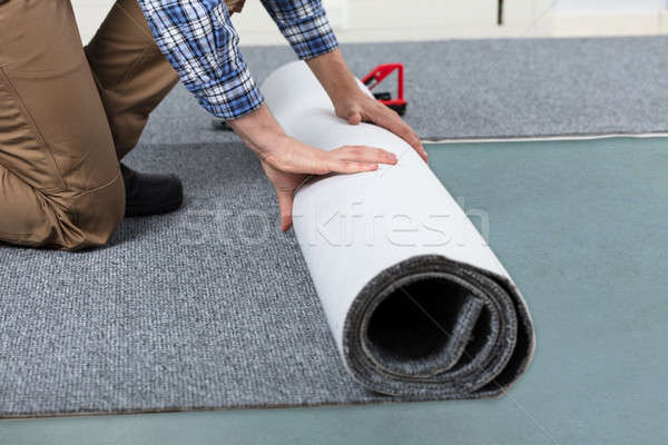 Male Handyman Rolling Carpet On Floor Stock photo © AndreyPopov