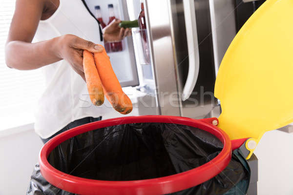 Woman Throwing Carrot In Trash Bin Stock photo © AndreyPopov