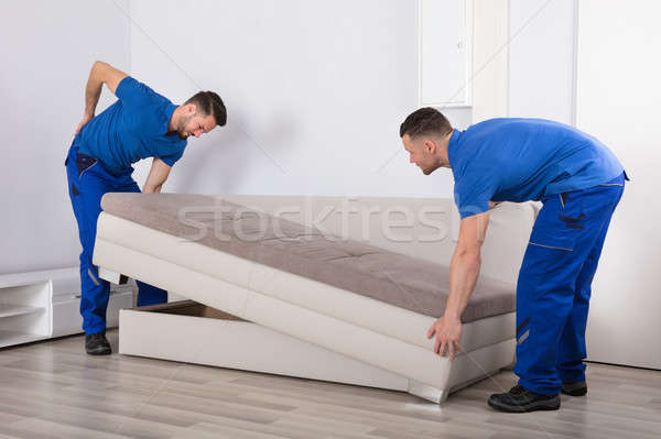 Mover Looking At His Partner Suffering From Backpain Stock photo © AndreyPopov