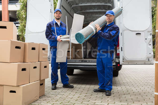 Two Delivery Men Holding Chairs And Carpet Stock photo © AndreyPopov