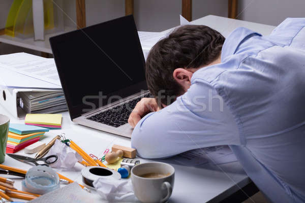 Exhausted Businessman Resting On Messy Desk With Open Laptop Stock photo © AndreyPopov