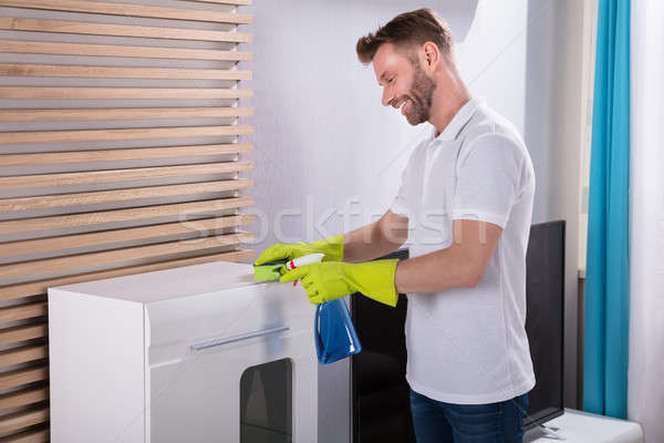 Young Man Cleaning Furniture With Spray Bottle Stock photo © AndreyPopov
