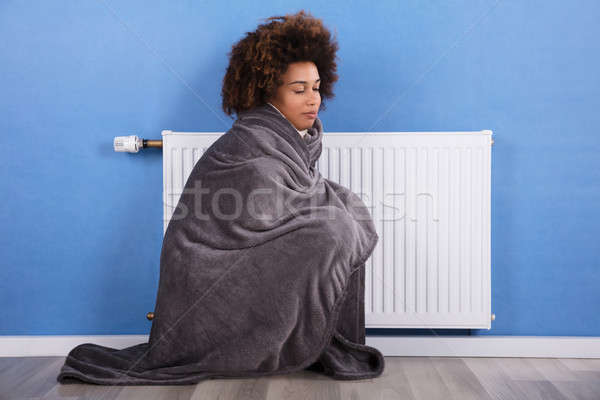 Woman Sitting Near Heater At Home Stock photo © AndreyPopov