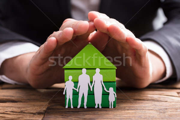 Businessperson Protecting House Model And Family Paper Cut Out Stock photo © AndreyPopov