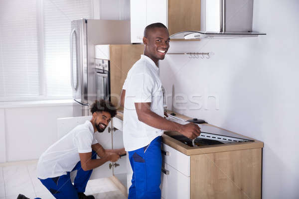 Two Young Handy Men Fixing The Equipment In The Kitchen Stock photo © AndreyPopov