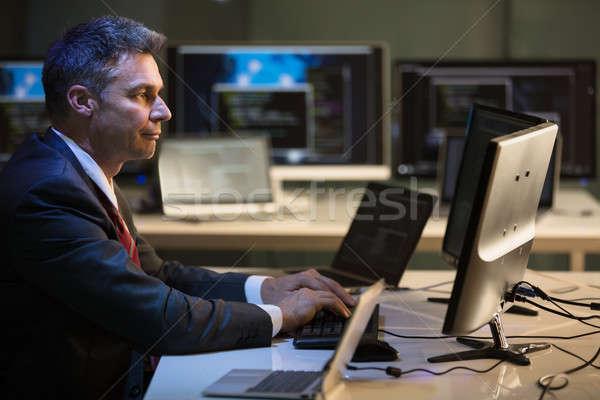 Imprenditore lavoro multipla computer vista laterale maturo Foto d'archivio © AndreyPopov