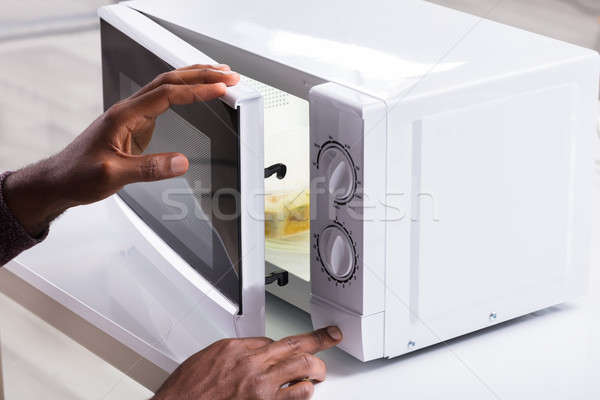 Man's Hand Heating Food In Microwave Oven Stock photo © AndreyPopov