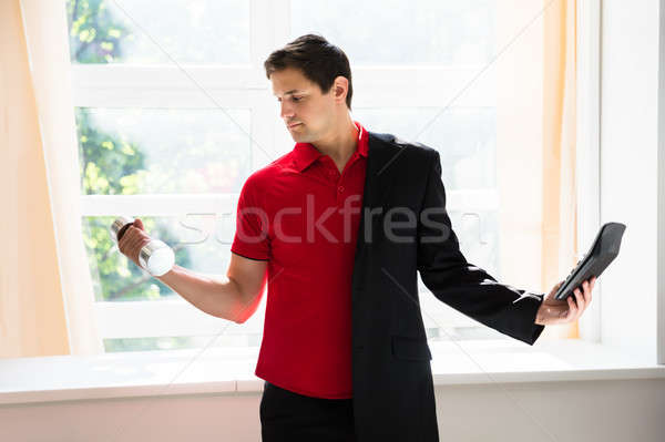 Businessman holding calculator exercising with dumbbell Stock photo © AndreyPopov