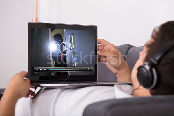 Man watching movie on laptop Stock photo © AndreyPopov
