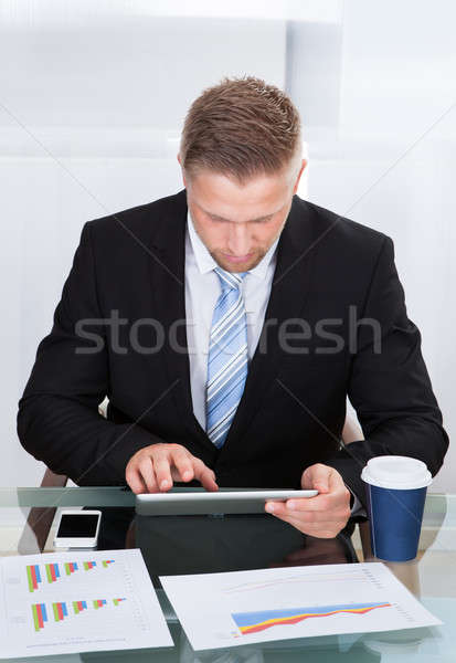 Stylish hardworking businessman using a tablet computer Stock photo © AndreyPopov