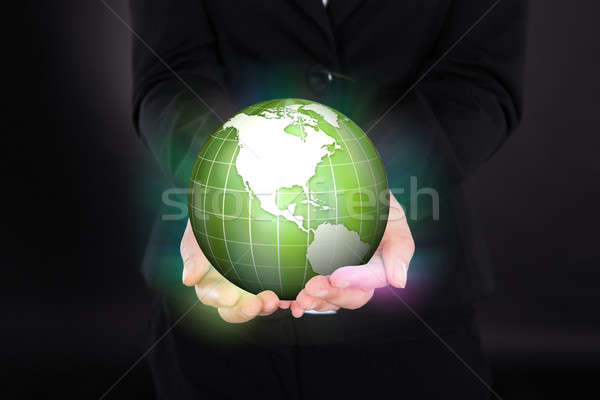 Businesswoman Holding Glowing Green Globe Stock photo © AndreyPopov