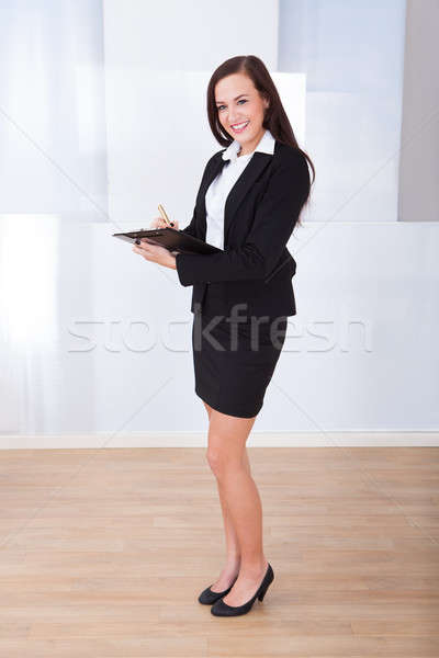 Welldressed Businesswoman Writing On Clipboard Stock photo © AndreyPopov