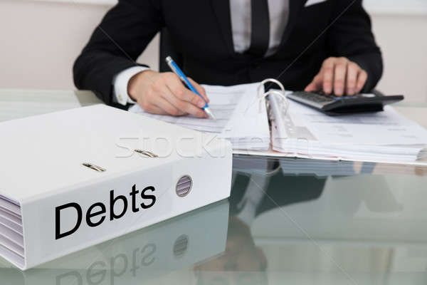 Businessman Calculating Debts At Desk Stock photo © AndreyPopov