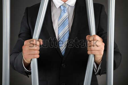 Businessman Bending Bars Of Jail Stock photo © AndreyPopov