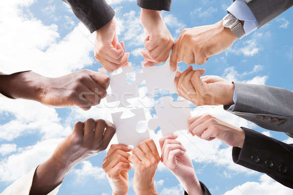 Multiethnic Business People Assembling Jigsaw Puzzle Against Sky Stock photo © AndreyPopov