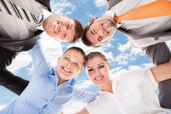 Happy Business People Forming Huddle Against Sky Stock photo © AndreyPopov