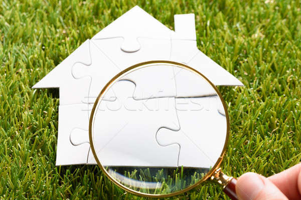Finger Holding Magnifying Glass Over Puzzle House Stock photo © AndreyPopov