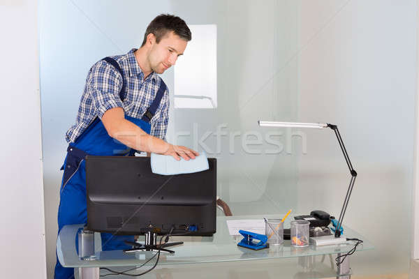 Male Janitor Cleaning Computer In Office Stock photo © AndreyPopov