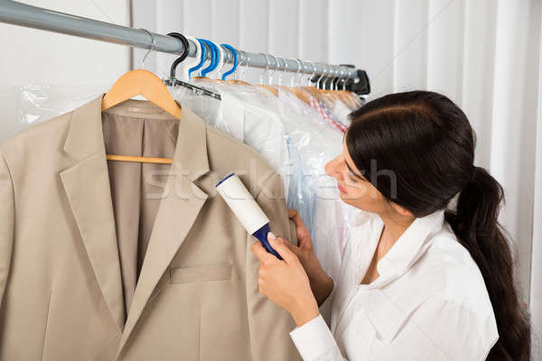 Stock photo: Cleaner In Laundry Shop With Adhesive Roller