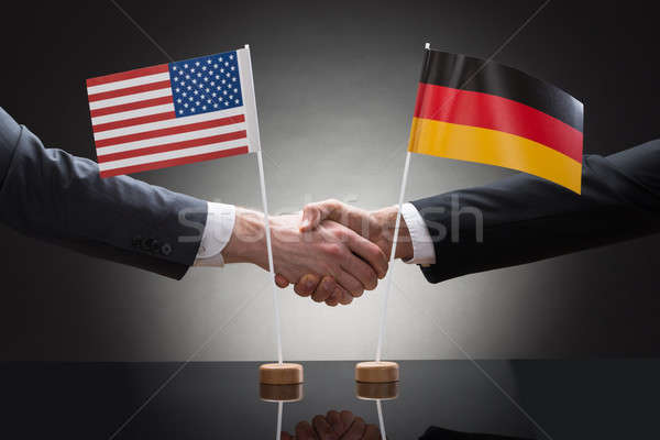 Businesspeople Shaking Hands With Us And Germany Flags Stock photo © AndreyPopov