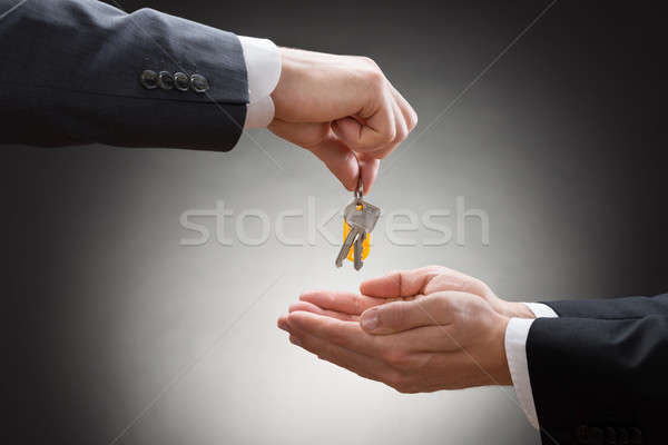 Stock photo: Close-up Of A Businessman's Hand Giving House Key