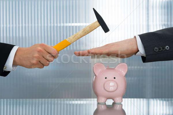 Businessman Saving Piggybank From Hammering Stock photo © AndreyPopov