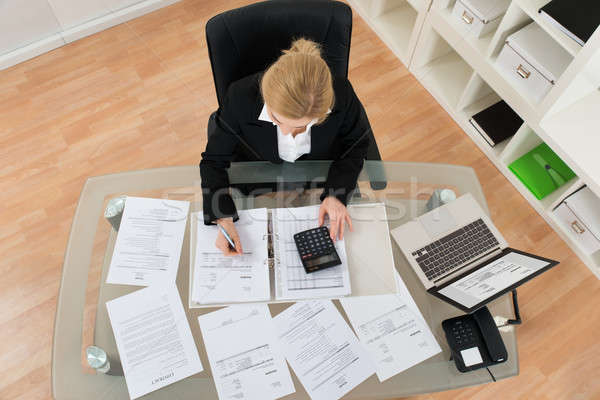 Businesswoman Calculating Invoices In Office Stock photo © AndreyPopov