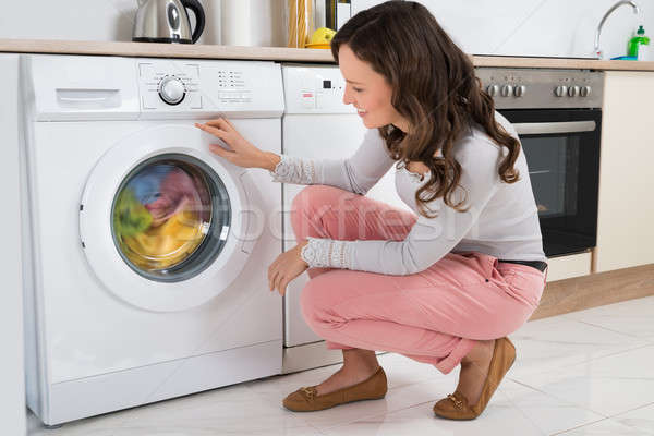Woman Looking At Clothes Rotating Inside The Washing Machine Stock photo © AndreyPopov