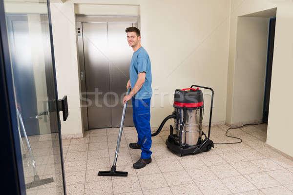 Maschio lavoratore pulizia aspirapolvere felice piano Foto d'archivio © AndreyPopov
