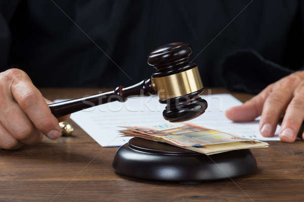 Judge Holding Gavel Over Banknotes At Desk Stock photo © AndreyPopov