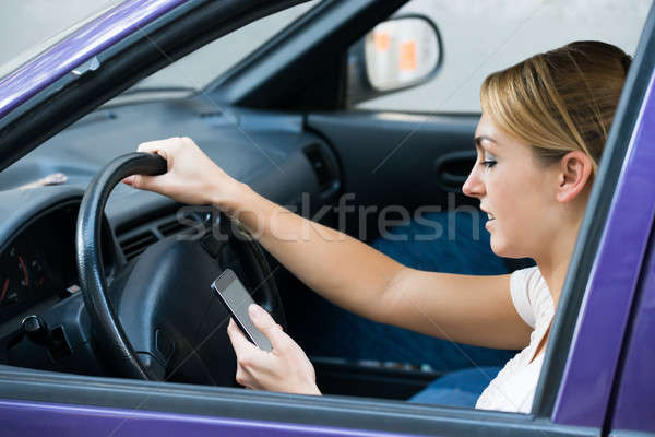 Vrouw mobiele telefoon rijden auto jonge vrouw telefoon Stockfoto © AndreyPopov
