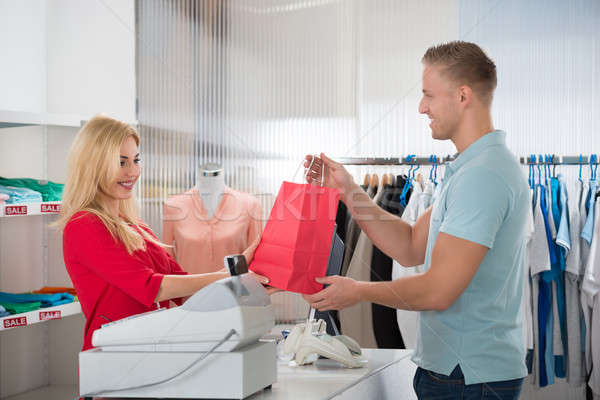 Happy Customer Taking Shopping Bag From Saleswoman In Store Stock photo © AndreyPopov