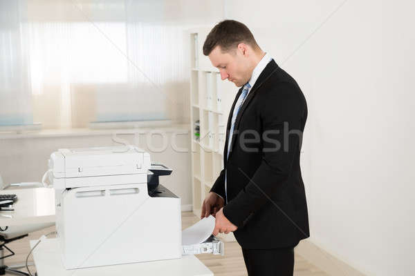 Businessman Inserting Paper In Photocopy Machine Stock photo © AndreyPopov