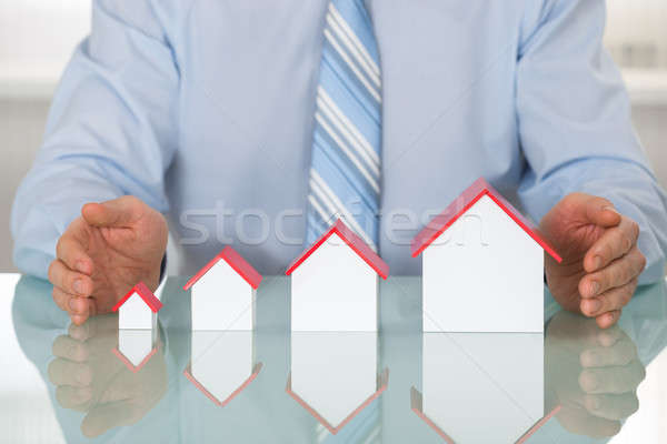 Businessman Protecting House Models Stock photo © AndreyPopov