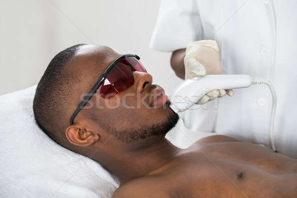 Therapist Giving Laser Epilation Treatment On Young Man Stock photo © AndreyPopov
