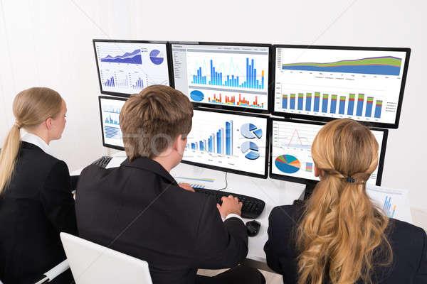 Gens d'affaires regarder financière graphiques multiple ordinateur Photo stock © AndreyPopov