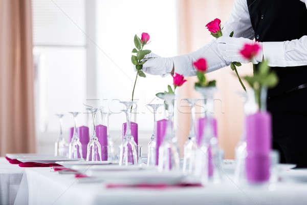 Waiter Arranging Roses In Vase Stock photo © AndreyPopov