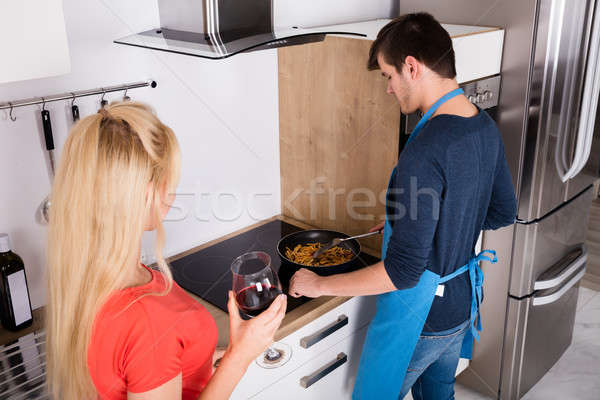 Woman Looking At Her Husband Preparing Dinner In Kitchen Stock photo © AndreyPopov