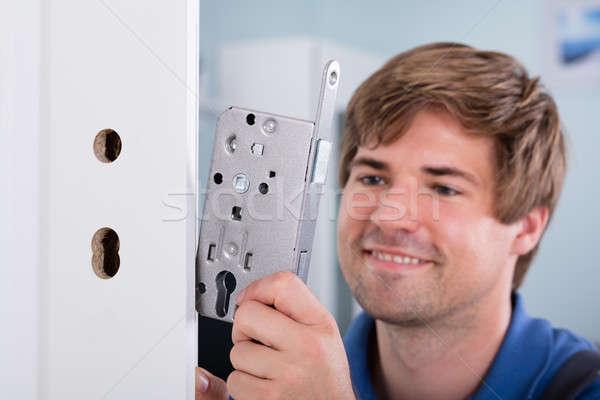 Man's Hand Installing Door Lock In Door Stock photo © AndreyPopov