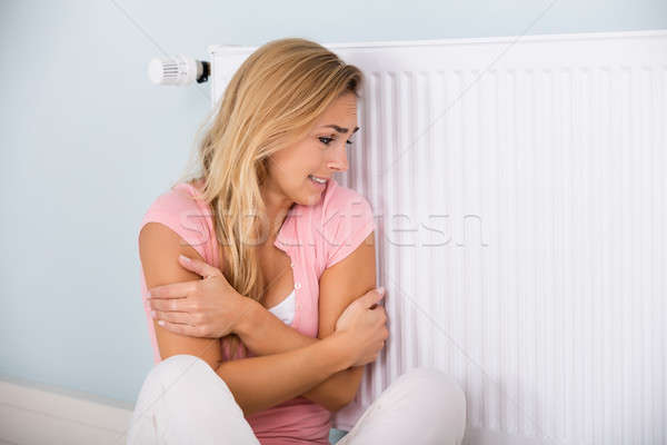 Woman Feeling Cold Sitting Near Thermostat Stock photo © AndreyPopov