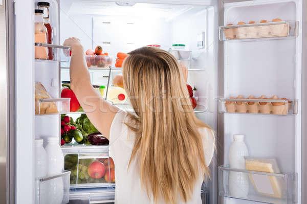 Kobieta patrząc żywności lodówce widok z tyłu młoda kobieta Zdjęcia stock © AndreyPopov