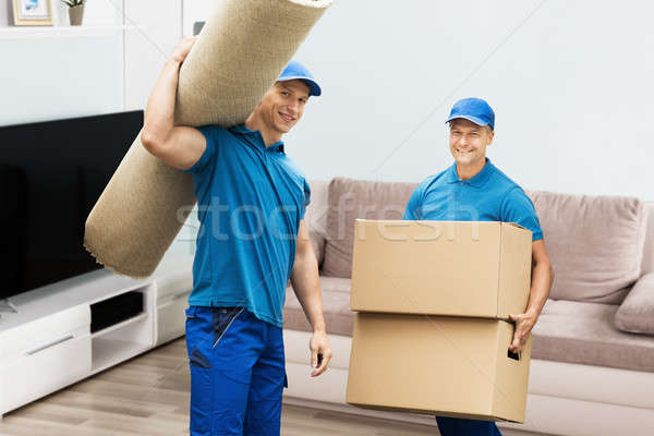 Stock photo: Two Male Workers Carrying Carpet And Cardboard Boxes