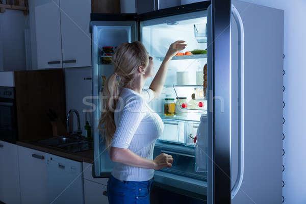 Mujer búsqueda alimentos refrigerador pie Foto stock © AndreyPopov